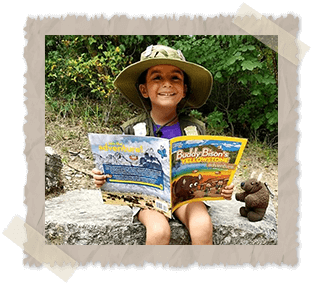 Little girl sitting outside on a rock reading Buddy Bison's Yellowstone Adventure